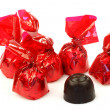 Bonbons wrapped in red shiny paper and one unwrapped ready to eat — Foto de Stock