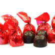 Stock Photo: Row of bonbons wrapped in red shiny paper and three unwrapped ready to eat