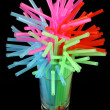 Long drink glass with some water and many colored plastic straws — Stock Photo