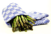Cooked asparagus drying in a old fashioned blue checkered kitchen towel — Stock Photo