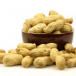 A bunch of fresh roasted peanuts in and around a brown bowl — Stock Photo
