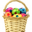 Wicker basket filled with colorful easter eggs - Stock Photo