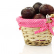 Fresh plums in a wicker basket with pink dotted cloth — Stock Photo