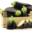 Stock Photo: Fresh aubergines and cut one in wooden crate