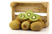 Green kiwi fruit and some cut ones in a wooden box — Stock Photo