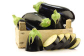 Fresh aubergines and a cut one in a wooden crate — Stockfoto