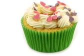 Bizcocho casero con crema y coloridos dulces corazones — Foto de Stock