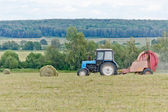 Harvester and haystacks — Stock Photo