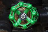 Green rusty industrial faucet wheel — Stock Photo