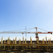 Building crane and building under construction against blue sky — Stock Photo #11858080