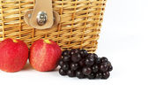 Grapes and apples in front of wicker basket for a picnic. — Stock Photo