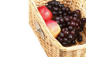 Apples and grapes in wicker basket. — Stock Photo