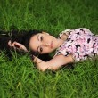 Portrait of young beautiful woman on a grass — Stock Photo