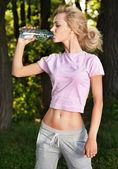Porträt des jungen fitness frau mit einer flasche wasser — Stockfoto