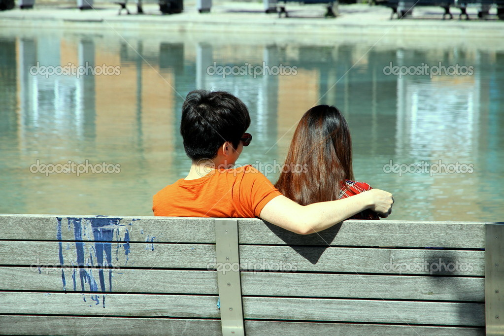 A young couple sitting on a bench — Stock Photo #10801250