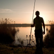 Fisherman silhouette at sunset — Stock Photo