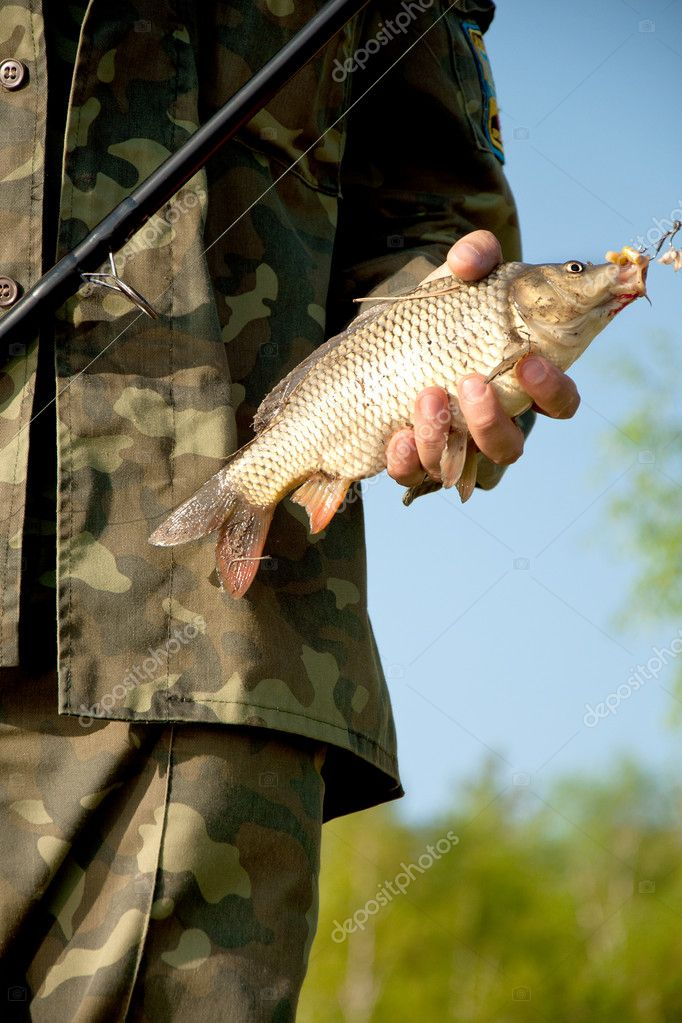 Close-up hands of fisher with the fish near the lake — Stock Photo #11528969