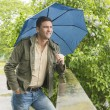 Man in park with blue umbrella — Stock Photo