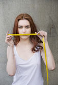 Young woman holding measuring tape — Stock Photo