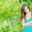 Beautiful woman outdoors with arms crossed against green backgro - Stock Photo