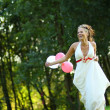 Young beautiful bride runs with balloons in hand - Stock Photo