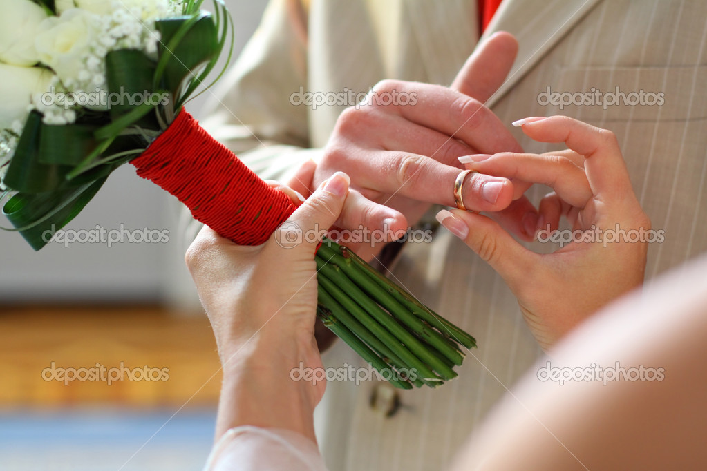 Bride putting a wedding ring on groom&#039;s finger  Stock Photo #10773706