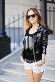 Açık havada poz güneş gözlüklü genç güzel kadın — Stok fotoğraf