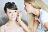 Young beautiful bride applying wedding make-up by make-up artist — Stock Photo
