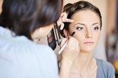 Giovane bella sposa applicando sposa make-up di truccatore — Foto Stock