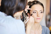 Young beautiful bride applying wedding make-up by make-up artist — Stok fotoğraf