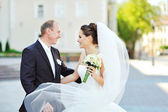 Young happy bride and groom having a good time in an old town — Stock Photo