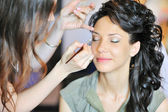 Young beautiful bride applying wedding make-up by make-up artist — Foto de Stock