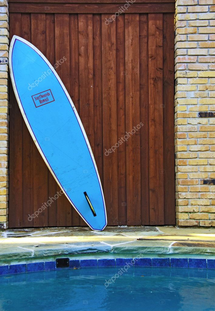 Surf Board once used for surfing has been retired to the pool as decoration.  Stock Photo #11086030