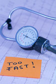 Medical stethoscope lying on ECG diagram with TOO HIGH memo — Stock Photo