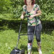 Smilling woman is mowing the grass — Stock Photo