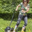 Stock Photo: Smilling womis mowing grass