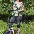 Smilling woman posing during mowing — Stock Photo