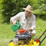 mediados de edad hombre añadiendo aceite a lawnmover — Foto de Stock