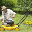 Mid age man repairing lawn mower - Stock Photo