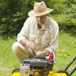 Stock Photo: Mid age man repairing lawn mower
