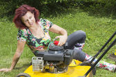 Smilling women oiling lawn mower — Stock Photo
