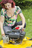 Smilling women oiling lawn mover — Stock Photo