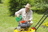 Mid age man adding oil to lawnmover — Stock Photo