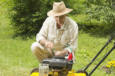 Mid age man repairing lawn mower — Stock Photo