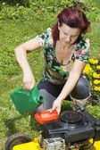 Women adding oil to lawn mover — Stock Photo