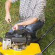 Man repairing yellow lawn mower Close up - Stock Photo
