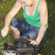 Cute girl repairing  yellow lawn mower — Stock Photo