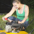 Cute girl oiling and repairing yellow lawn mower — Stock Photo #11341894