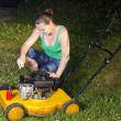 Cute girl repairing yellow lawn mower — Stock Photo #11341906