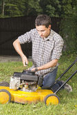 Repairing yellow lawn mover — Stock Photo